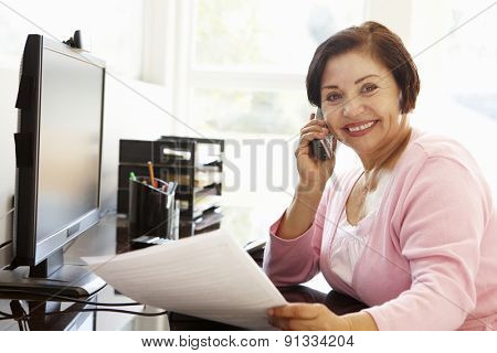 Senior Hispanic woman working on computer at home