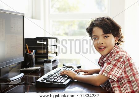 Young Hispanic boy using computer at home