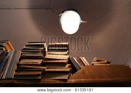 Many books on bookshelf with light bulb in library