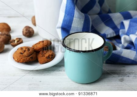 Milk in mug with walnuts and cookies on wooden background
