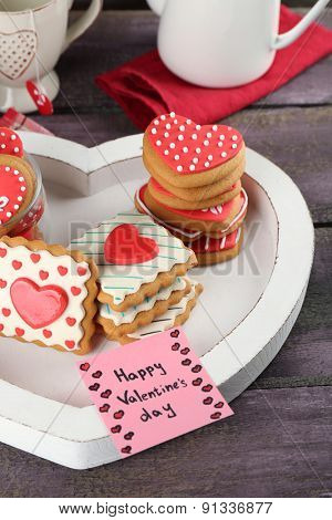 Heart shaped cookies for valentines day, cups on color wooden background