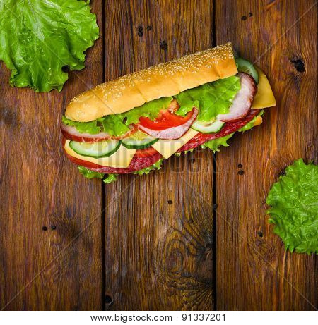 Sandwich With Meat And Vegetables On Wood