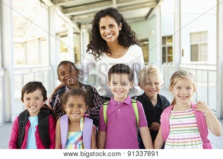 Group Of Elementary Age Schoolchildren Standing Outside With Teacher