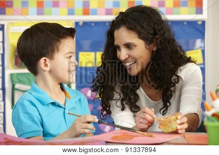 Elementary Age Pupil In Art Class With Teacher