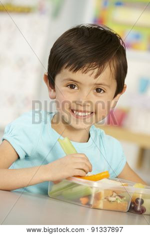 Elementary Age Schoolgirl Eating Healthy Packed Lunch In Class