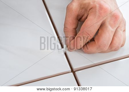 Person's Hand Placing Spacers Between Tiles