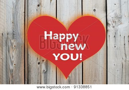 Happy new you message with red heart over wooden background