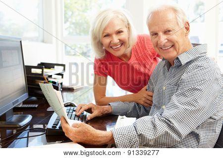 Senior man and daughter using computer at home