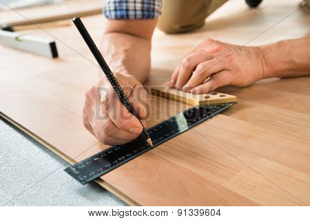 Worker Drawing A Mark On Laminate