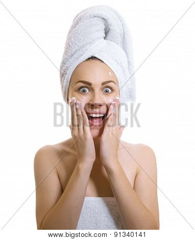 Surprised Woman Wrapped In A Towel Applaying Cream Or Moisturize On Her Cheek.expresive Female After