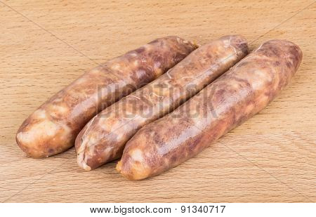 Three Raw Pork Sausages On Board