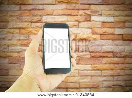 Hand Holding Smart Phone On Vintage Brick Wall Background
