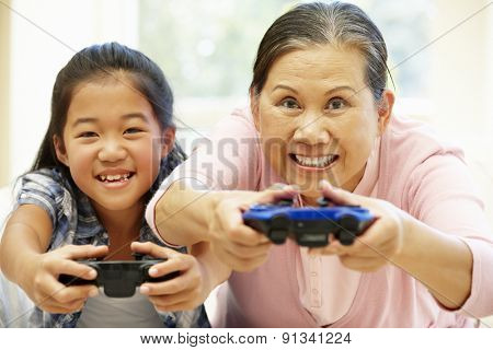 Senior Asian woman and girl playing video game