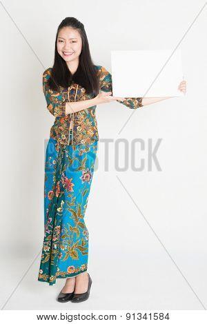 Full body portrait of Southeast Asian girl in batik dress hands holding white blank card, standing on plain background.