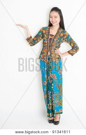 Full body portrait of Southeast Asian female in batik dress hand holding something standing on plain background.