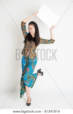 Full body portrait of Southeast Asian girl in batik dress hands holding white blank card jumping around on plain background.