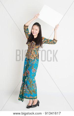 Full body portrait of Southeast Asian girl in batik dress hands holding white blank poster standing on plain background.