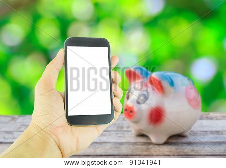 Hand Holding Smart Phone On Piggy Bank On Wooden Table Background