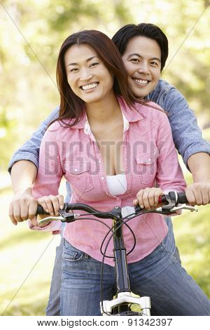Asian couple both sitting on one bicycle in park