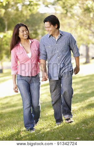 Asian couple walking hand in hand in park