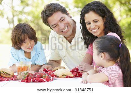 Young Hispanic Family Enjoying Picnic In Park