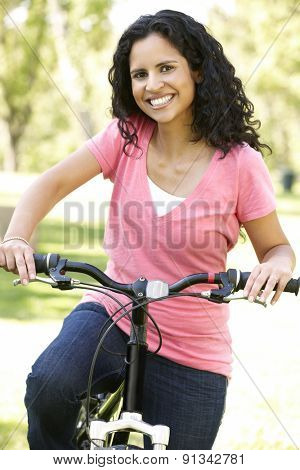 Young Hispanic Woman Cycling In Park