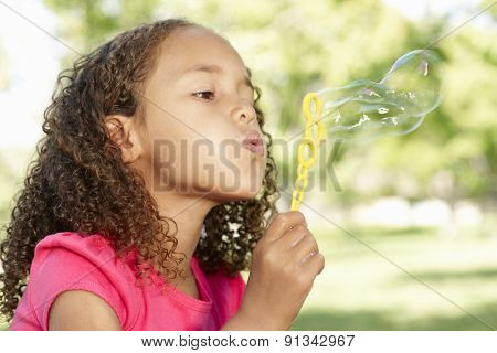 Young African American Girl Blowing Bubbles In Park