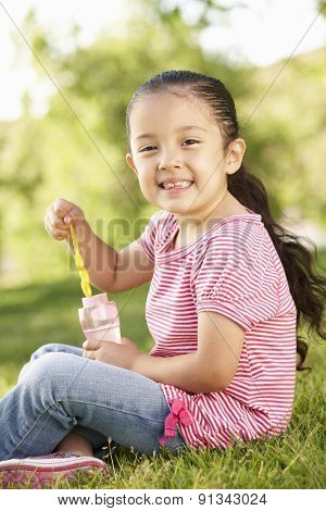Young Hispanic Girl Blowing Bubbles In Park
