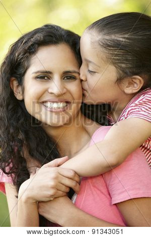 Hispanic Mother And Daughter Relaxing In Park