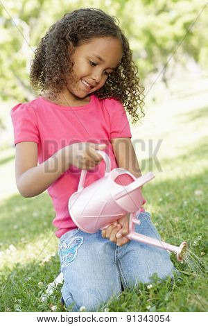 Young African American Girl With Watering Can In Park