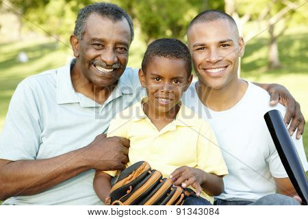 African American Grandfather, Father And Son Playing Baseball In Park
