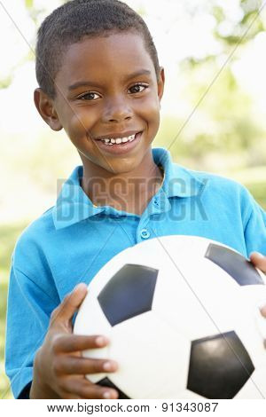 Young African American Boy Holding Football In Park