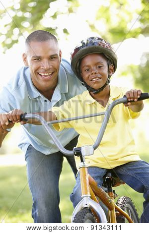 Father Teaching Son To Ride Bike In Park