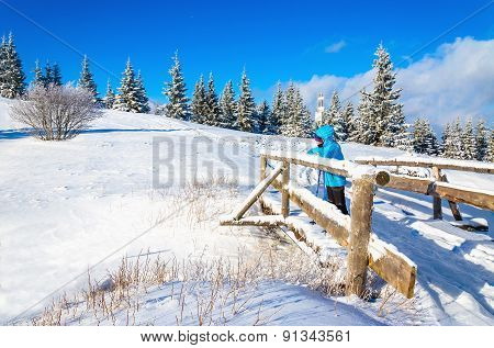 Beautiful winter landscape with womanon on bridge