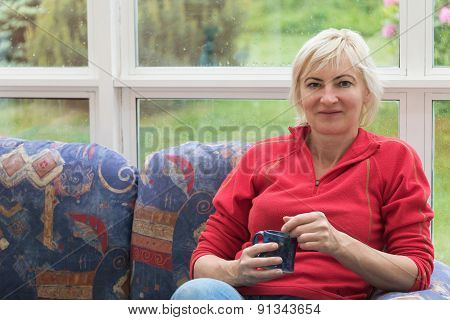 Blonde Middle-aged Woman Is Sitting On A Sofa