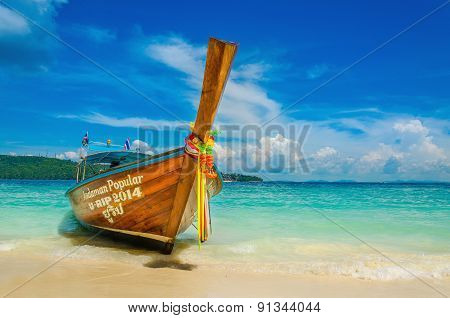 ongtailed boat against azure water of Andaman Sea