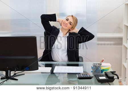 Businesswoman With Hands Behind Head At Desk