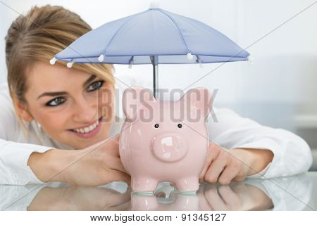 Businesswoman Sheltering Piggybank With Umbrella