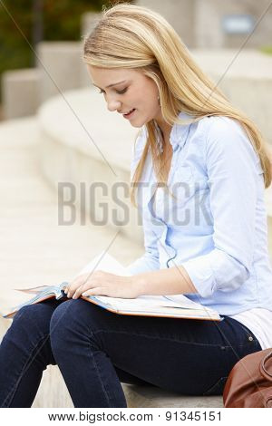 Teenage student reading outdoors