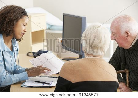 Young female Doctor talking to senior couple