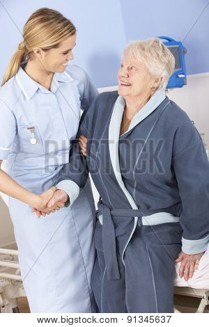 Nurse helping senior woman out of bed in hospital