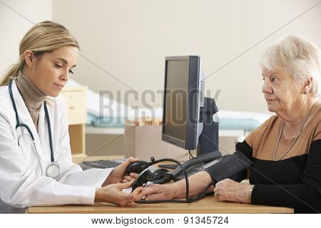 Doctor taking senior woman's blood pressure