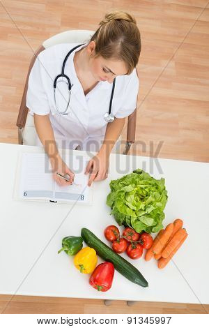 Female Dietician Writing In Diary