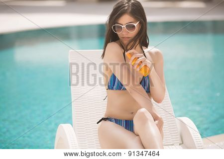 Woman applying sun cream to prevent sun spots,melanoma and UV radiation.Sexy brunette woman
