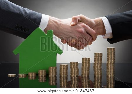 Businessmen Shaking Hands With Coins And House Model
