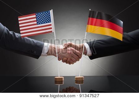Businesspeople Shaking Hands With Us And Germany Flags