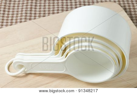 Four White Plastic Measuring Cups On Wooden Board