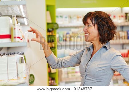 Smiling elderly woman buying cosmetics in a drugstore supermarket