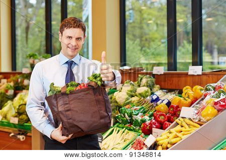 Happy man with shopping bag holding his thumbs up in a supermarket