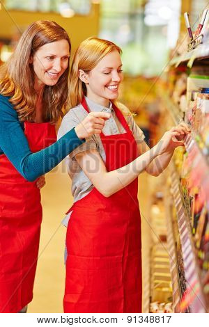 Storewoman in apprenticeship in supermarket getting help from elderly salesperson